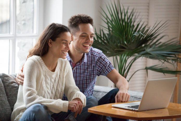 glückliches junges Paar, das lachendes lustiges Video lacht oder Videoanruf icrowdhouse 696x464 macht